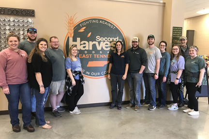 Farm Credit Scholars stand in front of Second Harvest sign