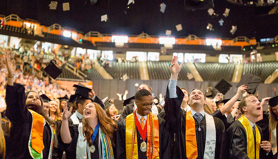 Graduates celebrating by tossing their caps in Thompson Boling Arena