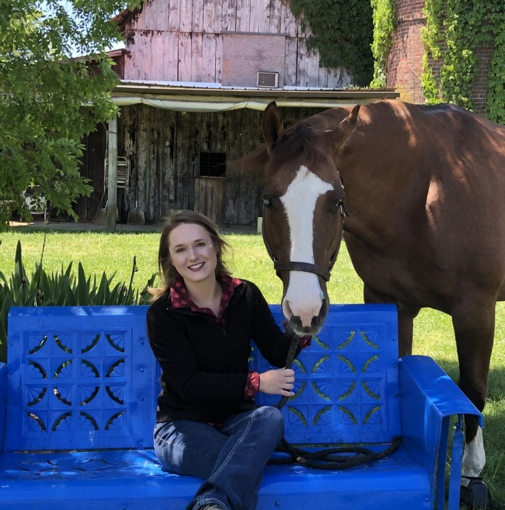 Delaney Rostad on an antique glider hold the reigns of a horse.
