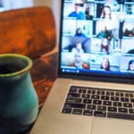 A coffee cup sits in front of an open laptop showing an online meeting.