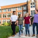 Four students from the Department of Agricultural Leadership, Education, and Communications walk together in front of Morgan Hall.